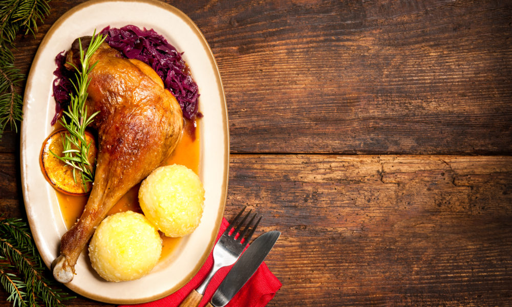 Crusty goose leg with braised red cabbage and dumplings. Cooking at Christmas time